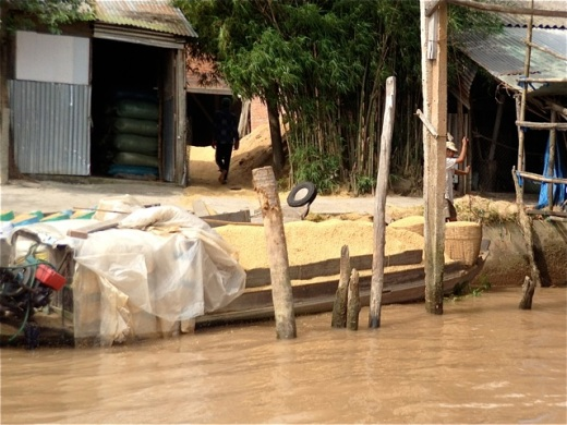 small rice barge loaded with baskets to sell at market in Vietnam